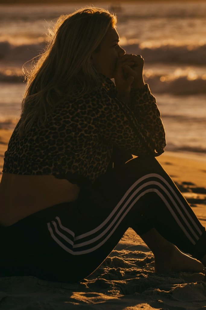 Woman sitting on a beach thinking about her past regrets
