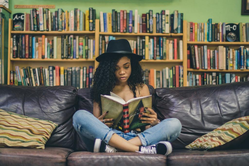 Woman in a library reading a personal development book on a black couch showing how to improve your life