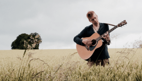 Geroge Francis playing a guitar in a field