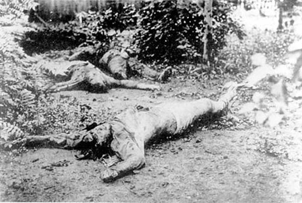 En primer plano, el cadáver del telegrafista Ponomarenko en la Cheka de Járkov, Ucrania. Le cortaron la mano derecha y muestra cortes profundos en la cabeza. Al fondo se ven los cadáveres de otras dos víctimas de los chekistas.