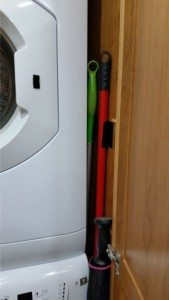 Broom And Mop Stored Next To Washer