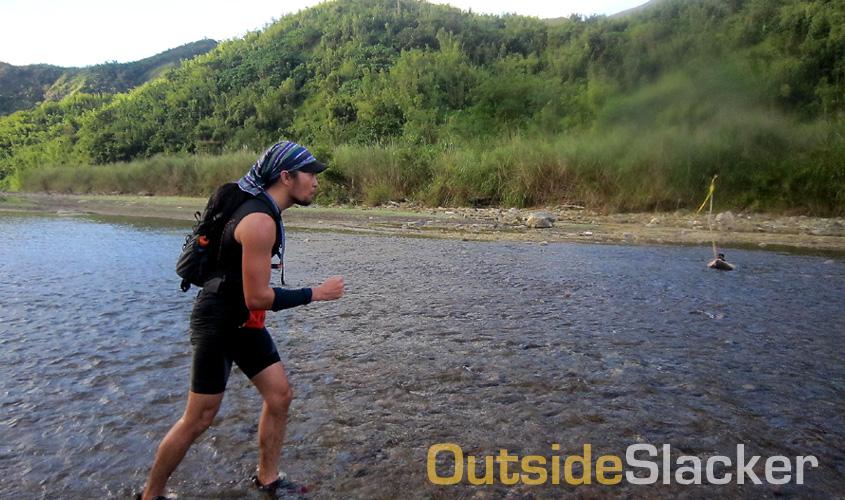 Trail runner crossing a stream during the Love a Tree Ultramarathon