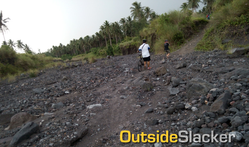 Bikers cross a dried up riverbed in Mayon