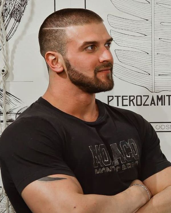 Muscly guy with buzzcut with parting