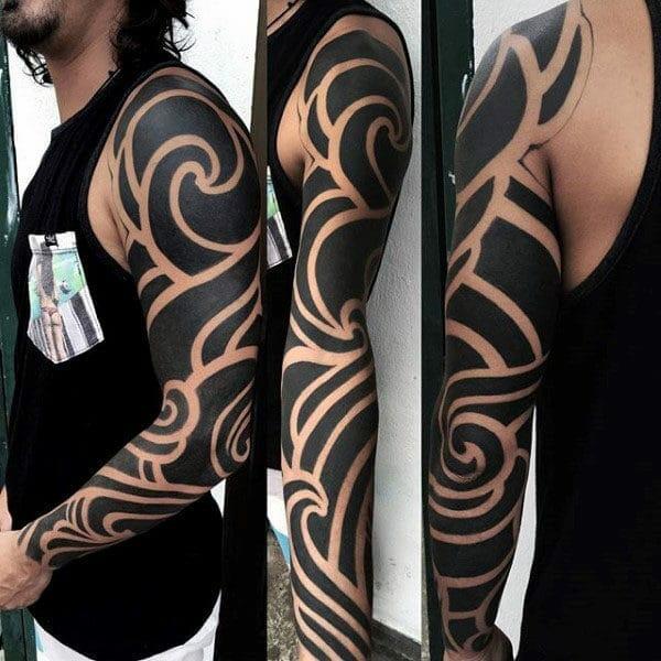 Blackwork Negative Space Full Sleeve Tribal Arm Tattoo