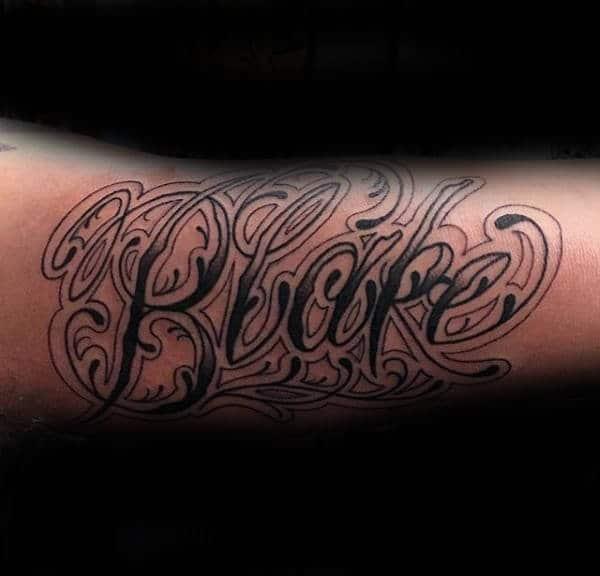 """Black"" Ornate Name Tattoo On Arm"