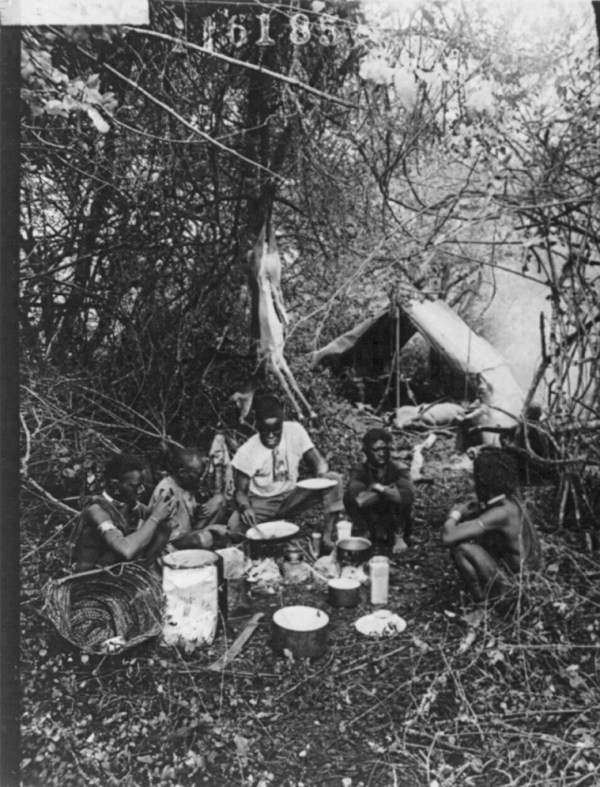 African Americans cooking in campsite, deer hanging from tree and an antelope lying by tent. 1909
