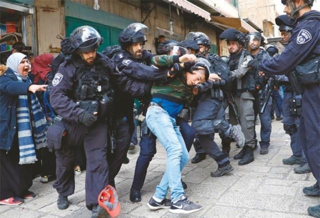 JERUSALEM: Israeli security forces detain a man in Old City on Friday.—AFP