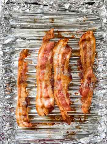 bacon cooking in the oven on tinfoil