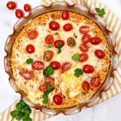 Baked eggs topped with cheese and cherry tomatoes