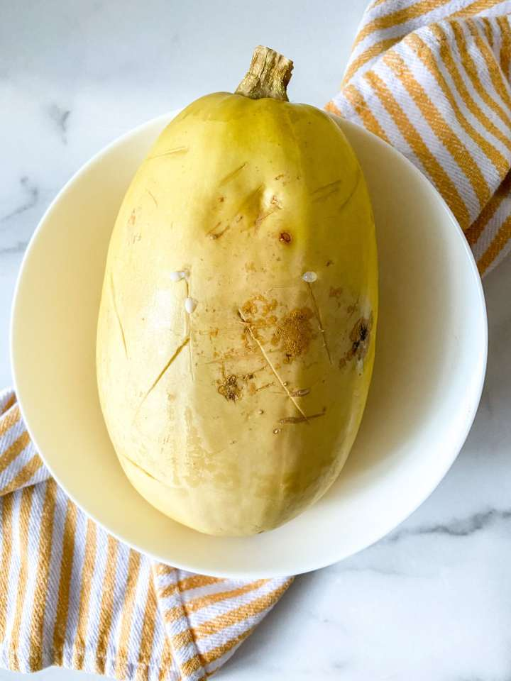 a cooked spaghetti squash in a white bowl on a yellow and white striped napkin
