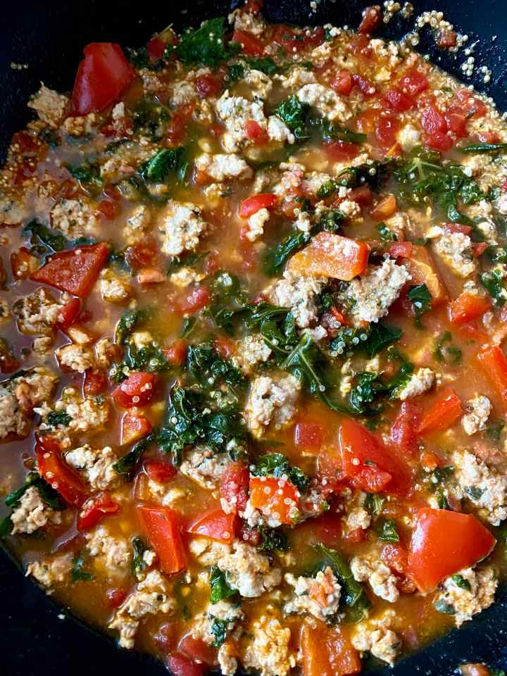 a large pot of chicken sausage, tomatoes, quinoa and kale