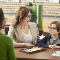 Mother and child discuss the child's glasses in front of a Pearle Vision employee.