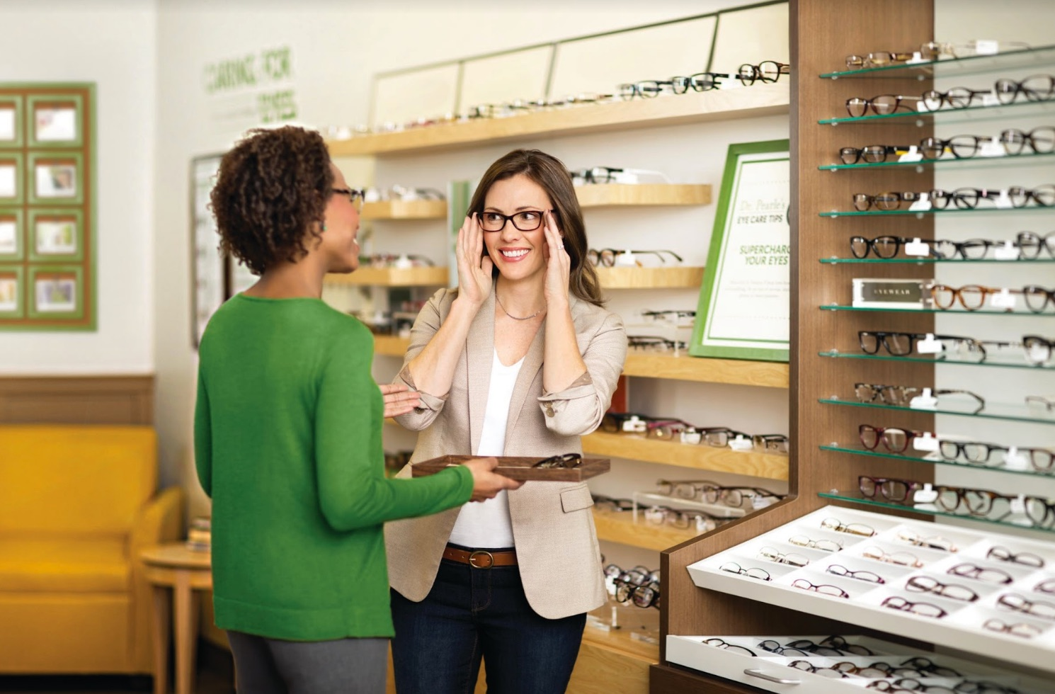 e895e5abc5 A sales associate helps a customer try on glasses in a Pearle Vision retail  store franchise