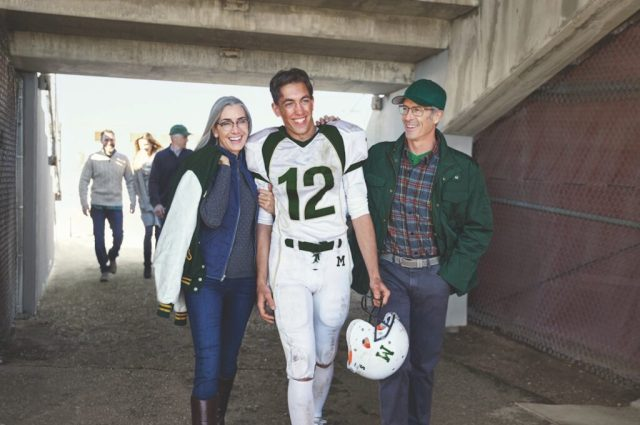 A young football player wearing the number 12 on his jersey in green is flanked by an older woman on his left and an older man on his right, both of whom are smiling and wearing glasses.