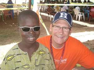 Optician and Pearle Vision Licensed Owner Gary Tonsager and a young participant of the Baseball in Benin program. Photo courtesy Baseball in Benin.