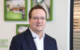 A portrait of Pearle Vision General Manager Alex Wilkes, with the Pearle Vision logo located in the lower-left corner.