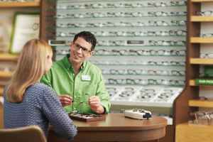 An optical retail sales associate sits at a table with a customer while showing her different pairs of glasses.