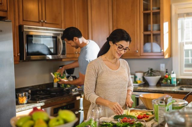 A smiling woman in glasses chops vegetables in her kitchen; visible but slightly out-of-focus in the background, her husband is pouring food into a skillet.