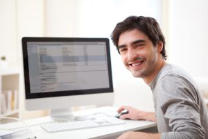View of a Young smiling man in front of computer