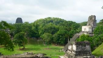 Guatemala, Tikal: Blick von der Acropolis Norte über den Plaza Grande auf die Acropolis Central. Rechts Tempel II und in der linken Bildhälfte aus dem Dschungel aufragend Tempel V