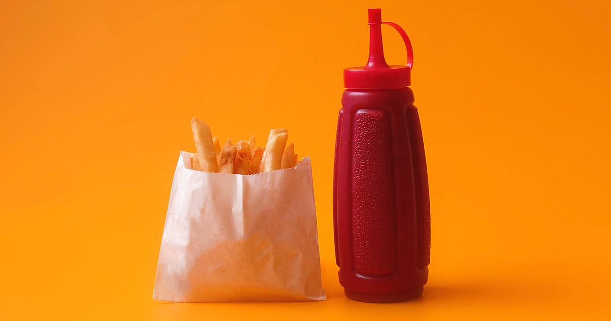 A packet of chips stands next to a ketchup bottle on an orange background