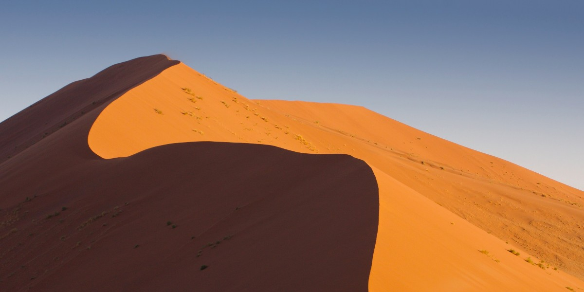 A sand dune in the desert with a blue sky behind it.