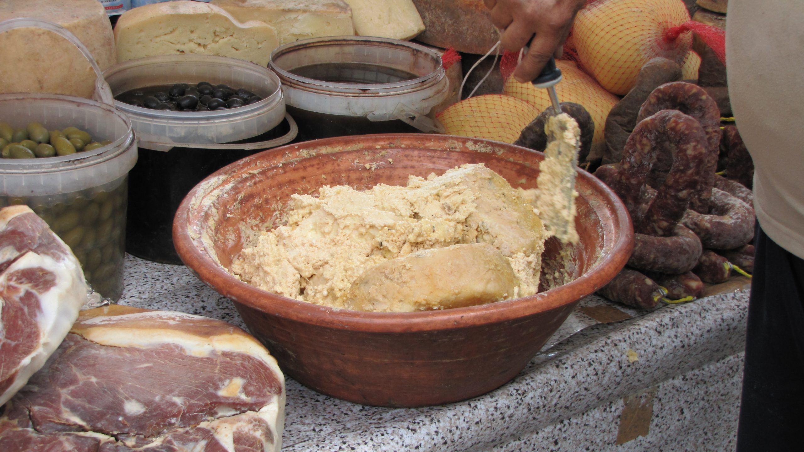 A brown ceramic bowl filled with casu marzu cheese surrounded by meats and buckets of olives