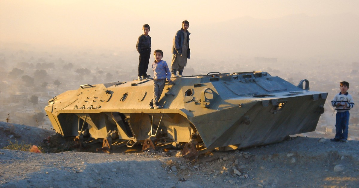 In Afghanistan, children play atop a tank carcass