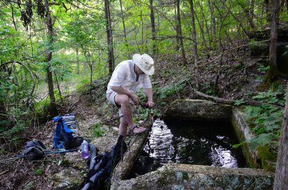 Photograph of Gary Allman filtering water using an MSR Sweetwater filter at Siloam Spring, Piney Creek Wilderness, Missouri