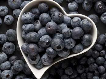 A heart-shaped bowl filled with blueberries.