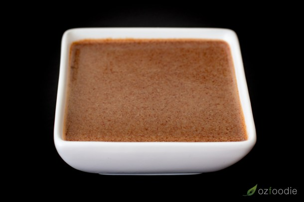 Hoisin sauce in a small square white bowl.
