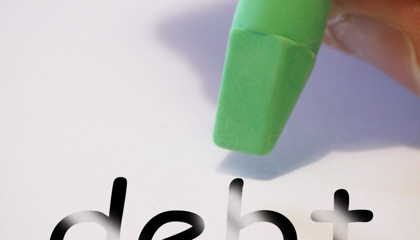 """the word """"debt"""" with a green eraser being held by a hand"""