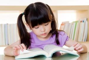 Little girl engaged in reading a book