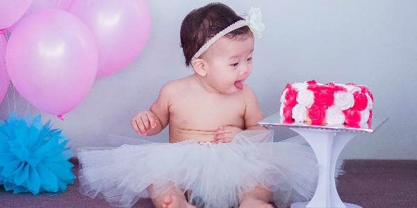 a chinese baby in a tutu marvels at a cake and the decorations around her, symbolizing the result of a well planned maternity leave and maternity insurance situation