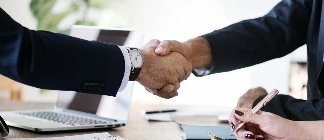 a businessman shakes hands with a benefits consultant