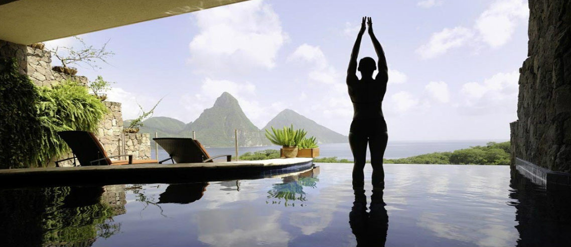 a woman stands in a yoga pose in front of a luxurious indoor pool as a fancy thai resort, representing wellness tourism