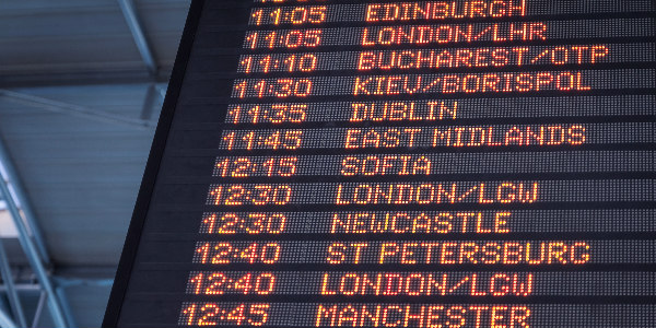 airport flight board showing international destinations as a sign for companies to consider managing risks better