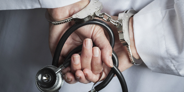 Close up shot of a doctors hands, clutching a stethoscope, handcuffed, relaying the idea that health care system fraud is a serious challenge
