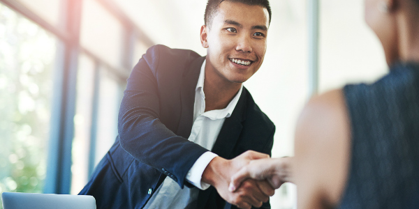 an employee benefits broker shakes hands with a client