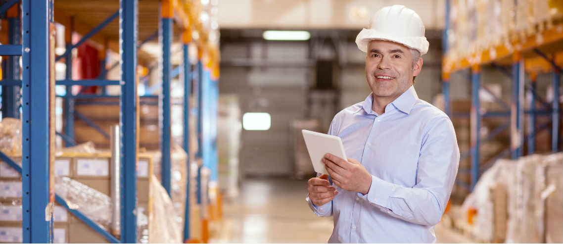 a gen x male manager stands with a hardhat in a warehouse, overseeing stock and inventory, symbolizing the need to understand the management benefits needs of gen x employees