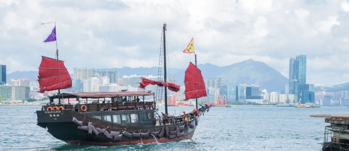 Sail boat going across the harbour in Hong Kong