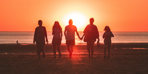 family reuniting on a beach in the sunset representing purchasing travel insurance for others
