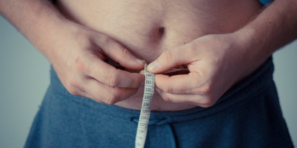 close up of a man pulling a measuring tape around his chubby belly, representing obesity in hong kong