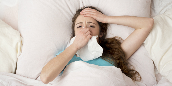 woman lies in bed holding her head and blowing her nose into a tissue as she fights off a cold without having full medical coverage