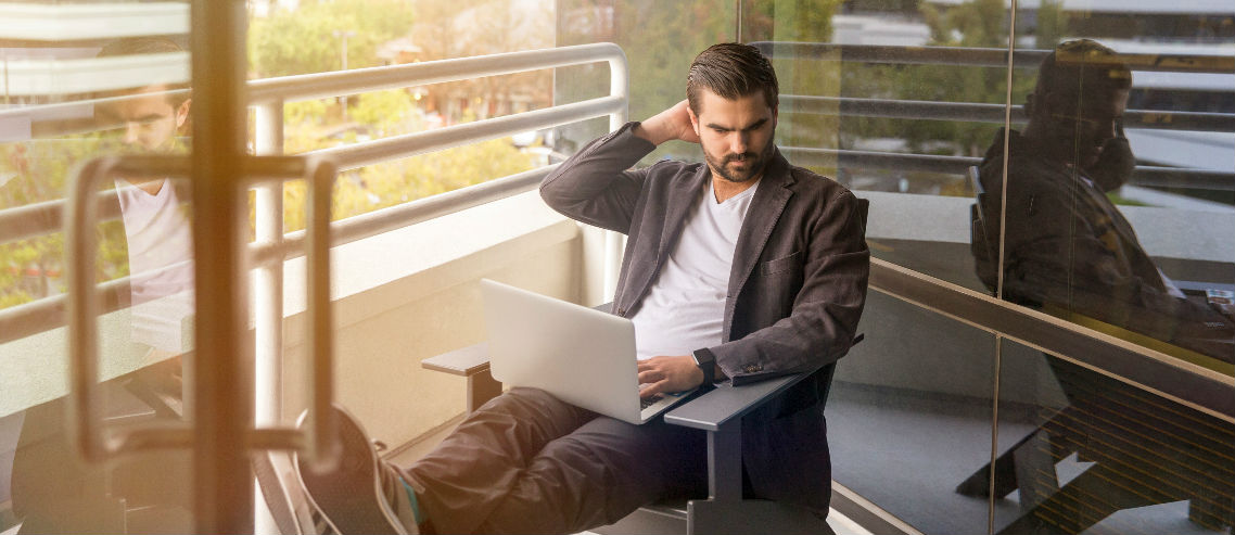 a man sits on a balcony with his laptop working out what his self employed insurance solution might be