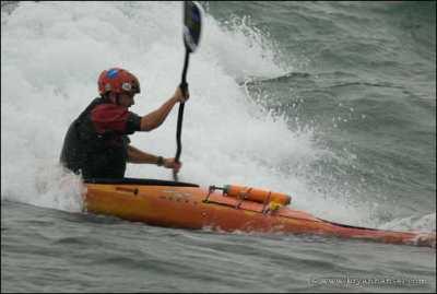 Kayaker in several feet of waves.