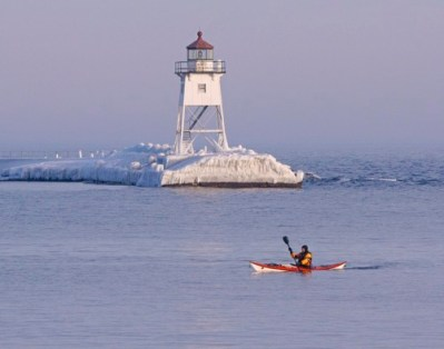 Kayaker paddling past the Grand Marais lighthouse in winter.