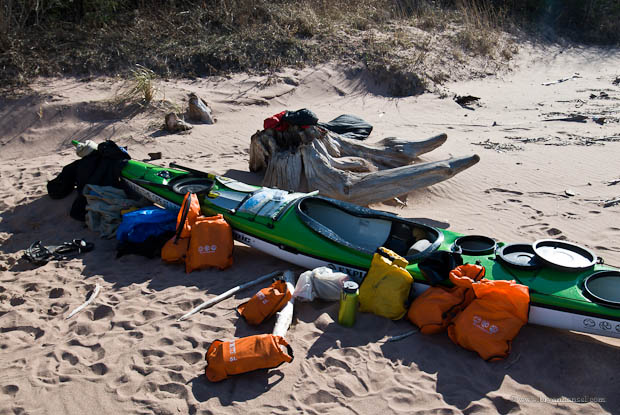 Packing a sea kayak with dry bags.