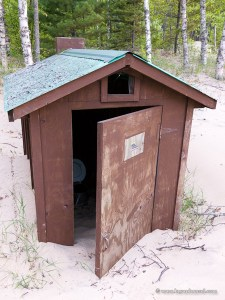 Outhouse buried in sand.